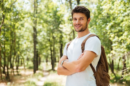 hapy: Happy confident young man with backpack standing with arms crossed in forest