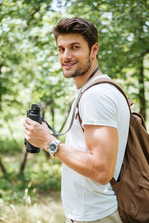 Happy young man with backpack standing and holding binoculars in forest