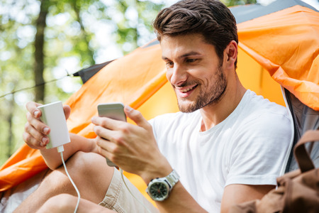 Happy young man tourist charging battery of mobile phone in touristic tent in forest Stock Photo