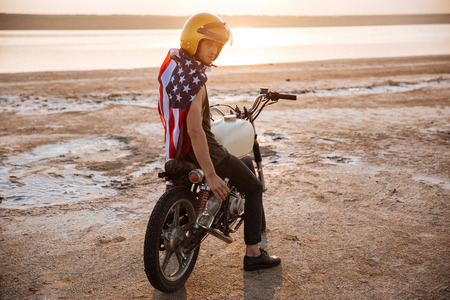 racer flag: Young brutal man in golden helmet and american flag cape sitting on his motocycle