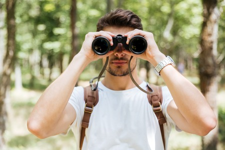using binoculars: Portrait of serious young man with backpack using binoculars in forest Stock Photo