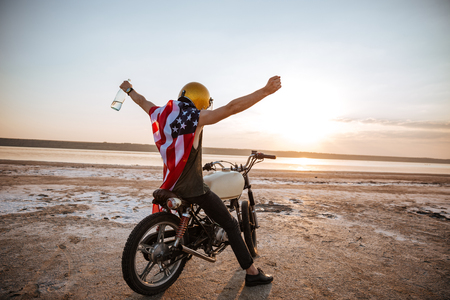 racer flag: Young brutal man in golden helmet and american flag cape sitting on his motocycle with hands up in the air