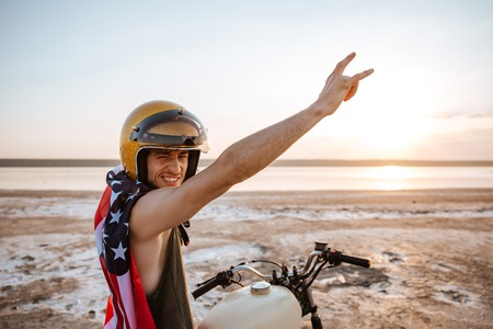 racer flag: Smiling brutal man in golden helmet and american flag cape sitting on his motocycle with hands up in the air