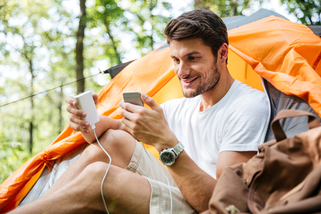 Cheerful young man tourist sitting and charging battery of mobile phone in touristic tent