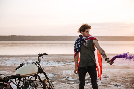 racer flag: Young brutal man wearing american flag cape holding smoke bomb at the desert