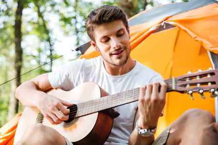 hapy: Happy young man tourist sitting in touristic tent and playing guitar in forest Stock Photo