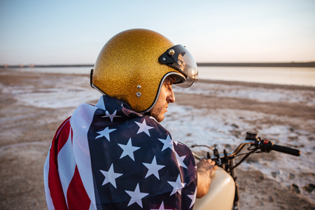 racer flag: Close up portrait of a brutal man wearing golden helmet and american flag sitting on motorcycle