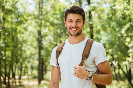 Closeup of cheerful young man in white t-shirt with backpack standing and smiling in forest