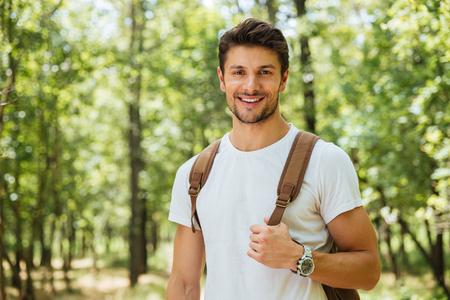 Close-up van de vrolijke jonge mens in witte t-shirt met rugzak die en zich in bos bevinden glimlachen