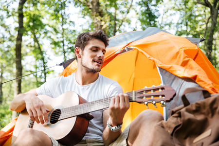 hapy: Smiling young man tourist sitting and playing guitar at touristic tent in forest