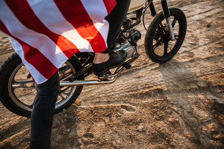 racer flag: Cropped image of men leg starting his motorcycle in desert