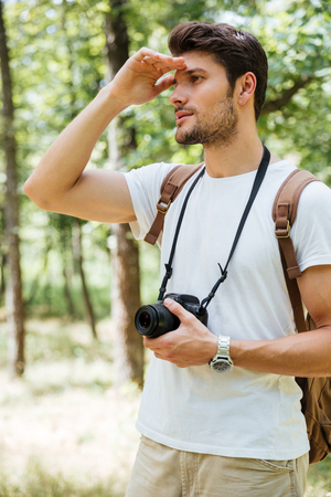 far away: Handsome young man photographer holding modern photo camera and looking far away in forest