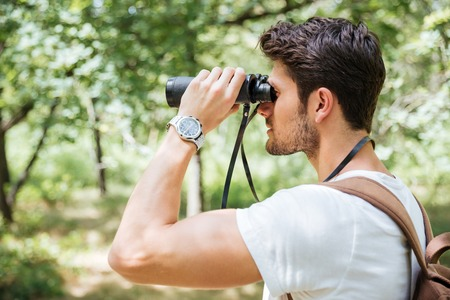 the watcher: Attractive young man with backpack looking through binoculars outdoors