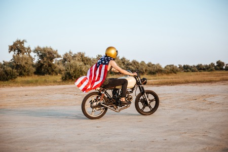 racer flag: Side view of a young brutal man in golden helmet and american flag cape driving retro motorcycle