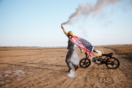 racer flag: Young brutal man wearing american flag cape and golden helmet holding smoke bomb at the desert