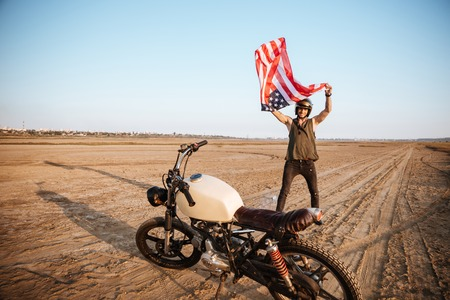 racer flag: Man in golden helmet waving american flag at the desert standing near motorcycle