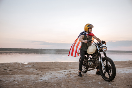 racer flag: Young brutal man in golden helmet and american flag cape driving retro motorcycle