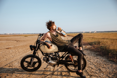 chrome man: Young brutal man laying on his motorcycle in the desert and drinking water
