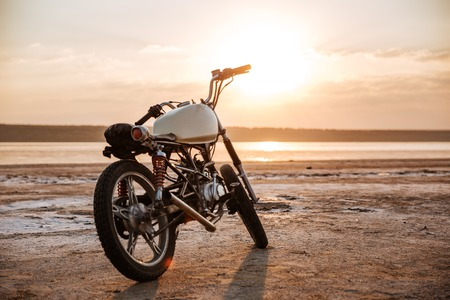 Retro motorcycle standing in the desert at sunset Stock Photo