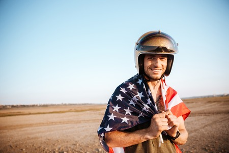 racer flag: Young smiling brutal man wearing american flag cape and golden looking at camera