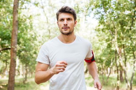 Geconcentreerde jonge man atleet met handband lopen buiten in de ochtend