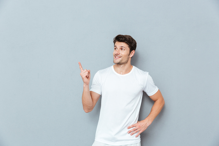 looking away from camera: Portrait of a casual man pointing fingers away over gray background