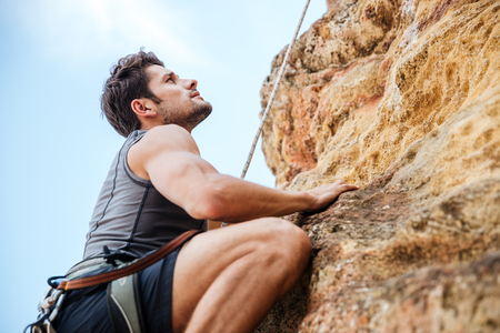 fearless: Young fearless man climbing a steep wall in mountain