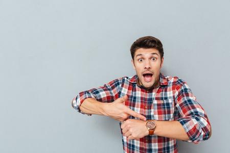 hombre joven sorprendente en camisa a cuadros que señala en el reloj de pulsera sobre fondo gris