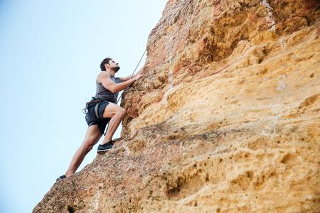 Junge Brünette Mann natürliche Felswand klettern