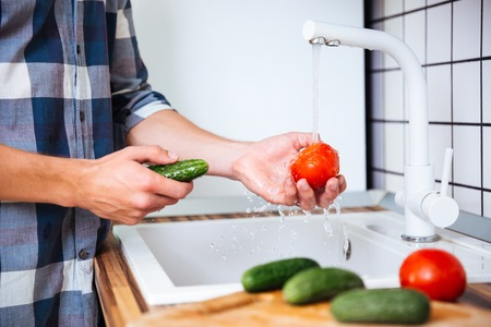 Closeup of young man in checkered shirt washing tomatoes and cucumbers on the kitchen