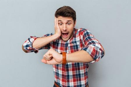 회색 배경 위에 손목 시계를보고 바둑판 된 셔츠에 놀란 된 젊은 남자