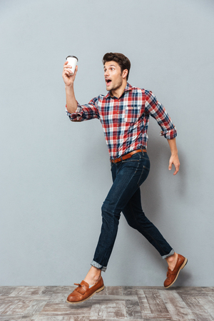 Attractive young man holding cup of takeaway coffee and running over grey background Stock Photo