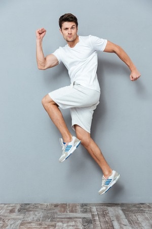 panicked: Funny young man jumping over gray background Stock Photo