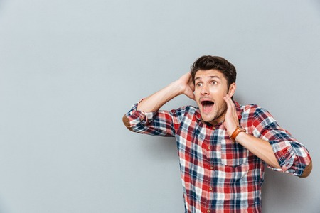unexpectedness: Stunned afraid young man in checkered shirt standing and shouting over grey background