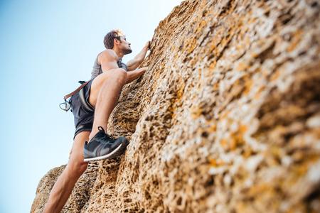 eine Felsenklippe Junge schönen Sportler klettern