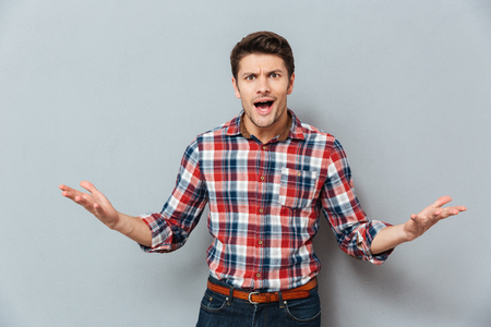 irritated: Angry irritated young man t-shirt over gray background Stock Photo