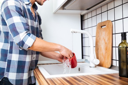 Closeup of young man in checkered shirt washing dishes on the kitchen