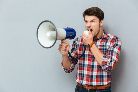 Irritated angry young man in plaid shirt shouting with loudspeaker over grey background Stock Photo