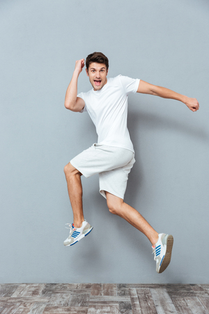 Funny crazy man jumping over gray background Stock Photo