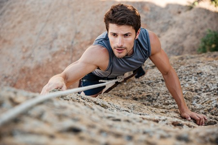 Man reaching for a grip while he rock climbs on a steep cliff Stock Photo