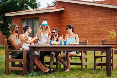 一群微笑的年轻人在户外的桌子上喝着啤酒和苏打水