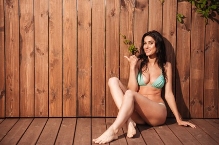 looking away from camera: Smiling sexy woman in bikini pointing finger away over wooden background