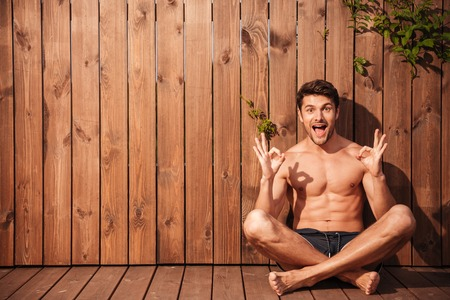 okay: Handsome young smiling man sitting and showing okay sign over wooden background Stock Photo