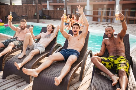 Knappe jonge lachende mannen plezier in het zwembad en het drinken van bier