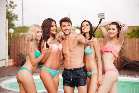 matress: Happy handsome young man and group of young women in swimsuits talking selfie with smartphone in summer Stock Photo