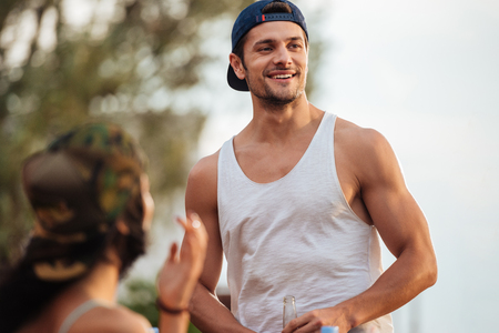 potrait: Potrait of smiling handsome young man in cap standing outdoors Stock Photo