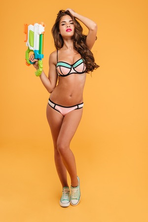 Full length portrait young beautiful sexy girl in bikini holding water gun and posing isolated on the orange background