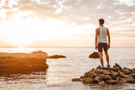 Young handsome man athlete standing backwards at the rocky beach by the sea