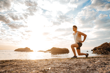 squats: Young healthy man athlete doing squats at the beach at sunset