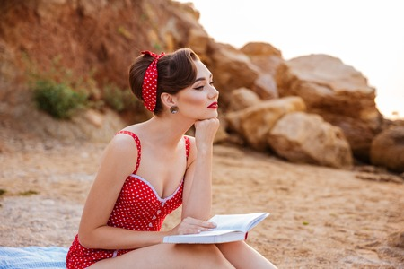 Young beautiful pensive pin up girl sitting with book at the beach